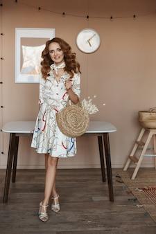Piękna młoda kobieta jest ubranym krótką lato suknię z kędzierzawym włosy i pozuje w domu w kuchni. koncepcja nowoczesnego mieszkania i wnętrza