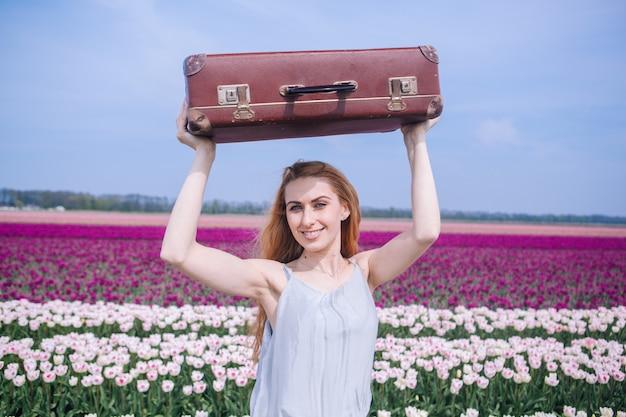 Piękna młoda kobieta jest ubranym w biel sukni pozyci z bagażem na kolorowym tulipanu polu z długim czerwonym włosy.