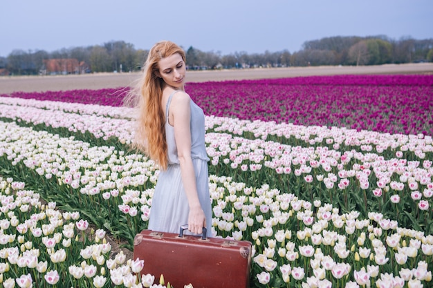 Piękna młoda kobieta jest ubranym w biel sukni pozyci z starą rocznik walizką na kolorowym tulipanu polu z długim czerwonym włosy.