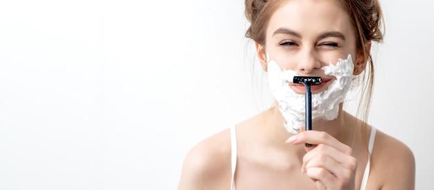 Piękna młoda kobieta kaukaski goli twarz brzytwą na białej ścianie. ładna kobieta z pianką do golenia na twarzy