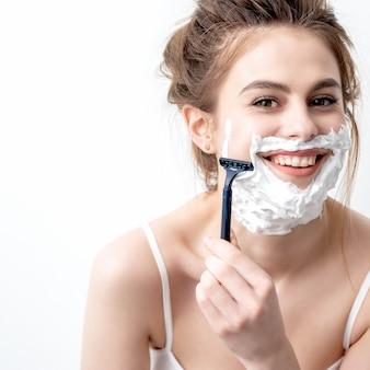 Piękna młoda kobieta kaukaski goli twarz brzytwą na białym tle. ładna kobieta z pianką do golenia na twarzy
