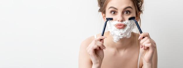 Piękna młoda kobieta kaukaski goli twarz dwiema brzytwami na białej ścianie. ładna kobieta z pianką do golenia na twarzy