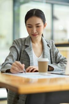Piękna młoda kobieta korzysta z laptopa i robi papierkową robotę