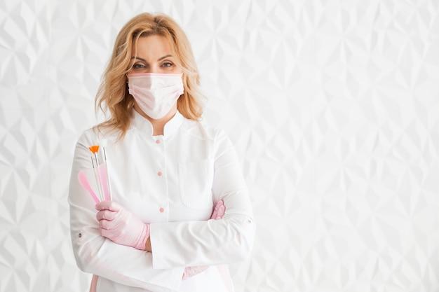 Piękna młoda kobieta kosmetyczka lekarz w białym mundurze i masce ochronnej na twarzy pozuje ze szczotkami w dłoniach.