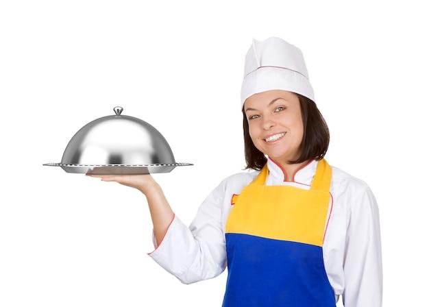 Piękna młoda kobieta kucharz z restaraunt cloche na białym tle