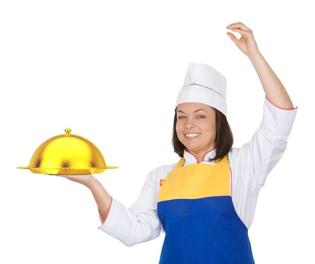 Piękna młoda kobieta kucharz ze złotym kloszem restauracji na białym tle