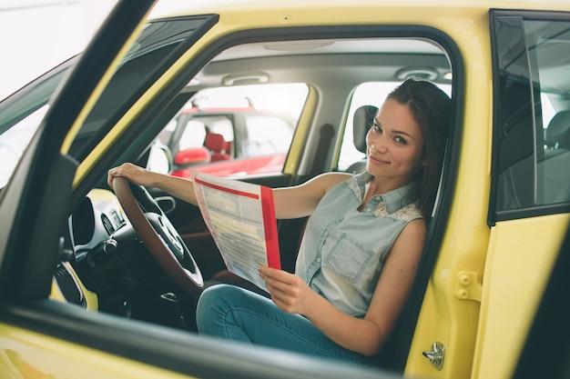 Piękna młoda kobieta kupuje samochód przy przedstawicielstwem handlowym.