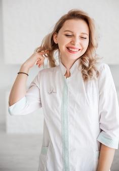 Piękna młoda kobieta lekarz pozowanie w białej sukni medycznej.