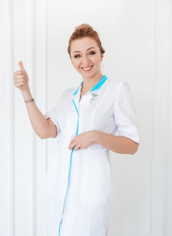 Piękna młoda kobieta lekarz pozowanie w białym fartuchu na tle białej ściany i pokazuje klasę.