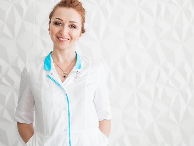Piękna młoda kobieta lekarz pozowanie w białym fartuchu na tle białej ściany.