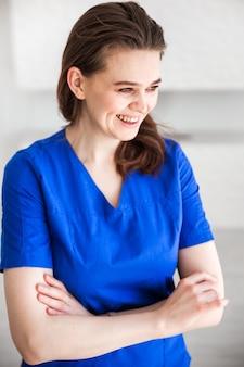 Piękna młoda kobieta lekarz pozowanie w niebieskim garniturze medycznym.