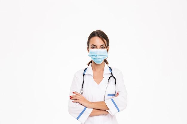 Piękna młoda kobieta lekarz ubrany w mundur stojący na białym tle nad białą ścianą, zakładając maskę