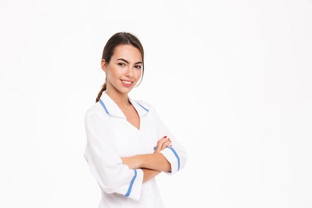 Piękna młoda kobieta lekarz ubrany w mundur stojący na białym tle nad białą ścianą