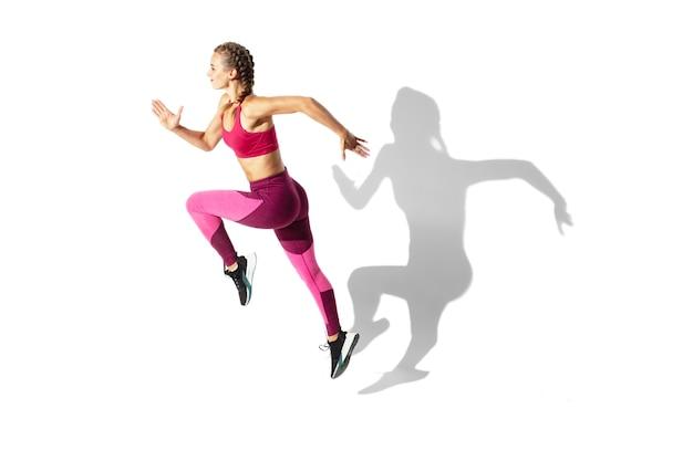 Piękna młoda kobieta lekkoatletka ćwiczy na białej przestrzeni, portret z cieniami