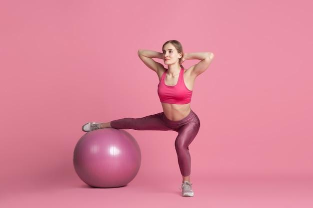Piękna młoda kobieta lekkoatletka ćwiczy na monochromatyczny portret różowej ściany