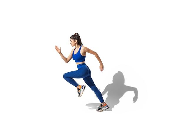 Piękna młoda kobieta lekkoatletka ćwiczy na tle białego studia, portret z cieniami. sportowy model w ruchu i akcji.