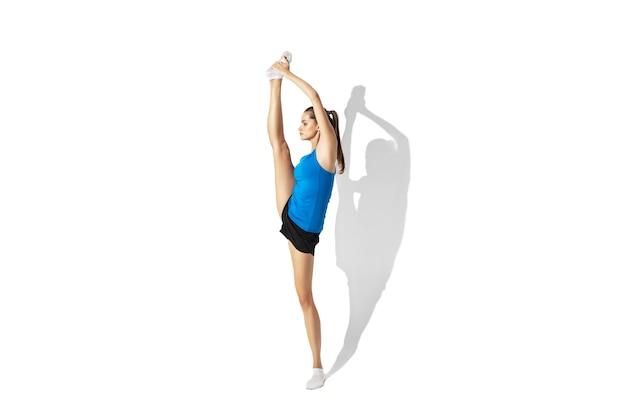 Piękna młoda kobieta lekkoatletka rozciąganie, trening na białej przestrzeni, portret z cieniami