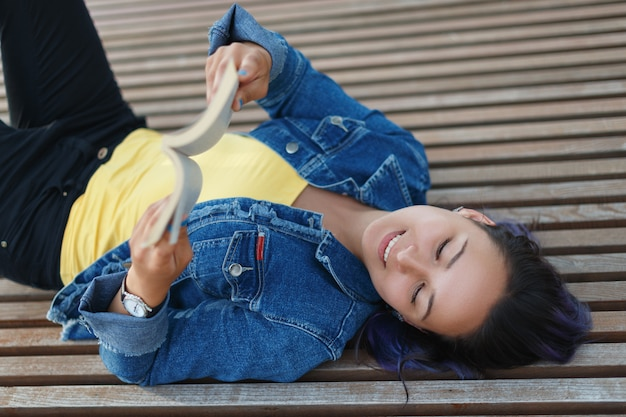 Piękna młoda kobieta, leżąc na ławce, uśmiechając się i czytając książkę