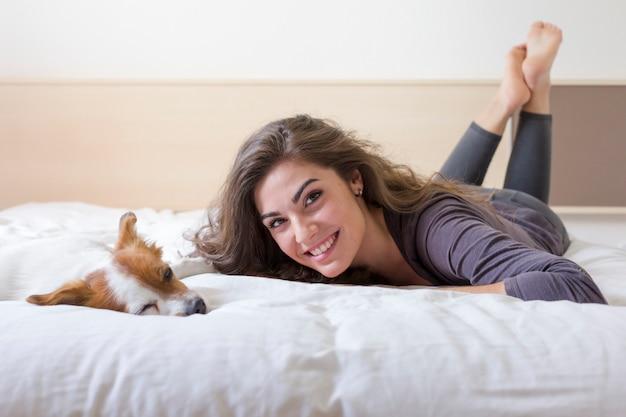 Piękna młoda kobieta, leżąc na łóżku z jej uroczym małym psem poza tym. dom, wnętrze i styl życia