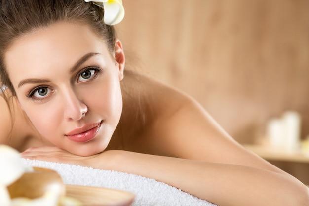 Piękna młoda kobieta, leżąc w salonie spa. koncepcja pielęgnacji skóry i ciała, zdrowego stylu życia, relaksu, masażu i kosmetologii