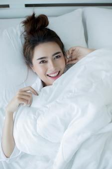 Piękna młoda kobieta leży w łóżku i śpi.