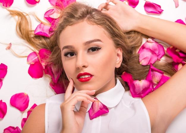 Piękna młoda kobieta leży w różowe płatki.