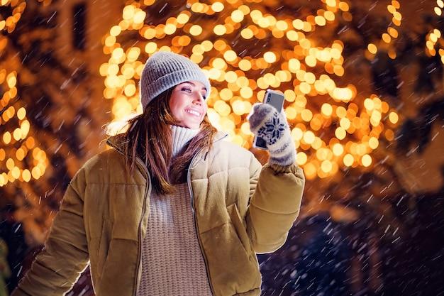 Piękna młoda kobieta lub kobieta robi selfie lub używa telefonu na zewnątrz