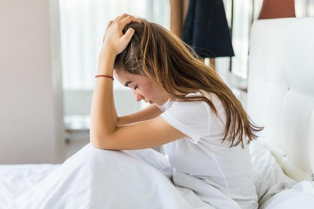 Piękna młoda kobieta ma ból głowy siedząc w łóżku
