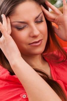 Piękna młoda kobieta ma ból głowy