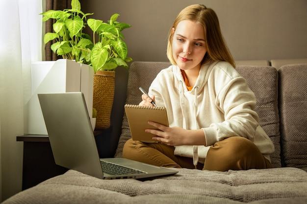 Piękna młoda kobieta ma edukację online na kanapie w domu. nastolatka uczy się zdalnie online z domu podczas blokady koronawirusa covid 19. praca freelancera na laptopie