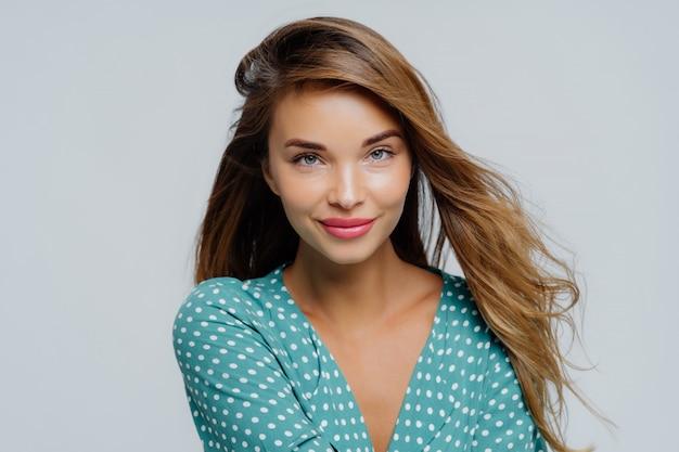 Piękna młoda kobieta ma makijaż, ubrana w koszulę polkadot