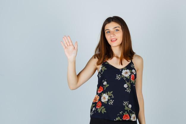 Piękna młoda kobieta macha ręką, aby pożegnać się w bluzce i patrząc wesoło