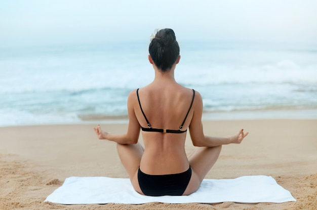 Piękna młoda kobieta medytacja w pozie jogi na plaży. dziewczyna ćwiczy jogę