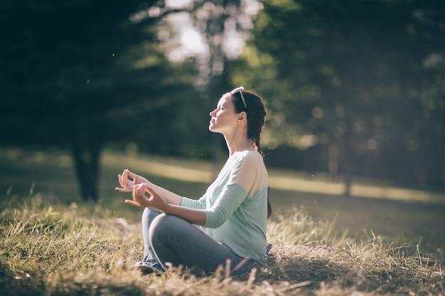 Piękna młoda kobieta medytacji w pozycji lotosu, siedząc na trawniku. zdjęcie z miejscem na kopię