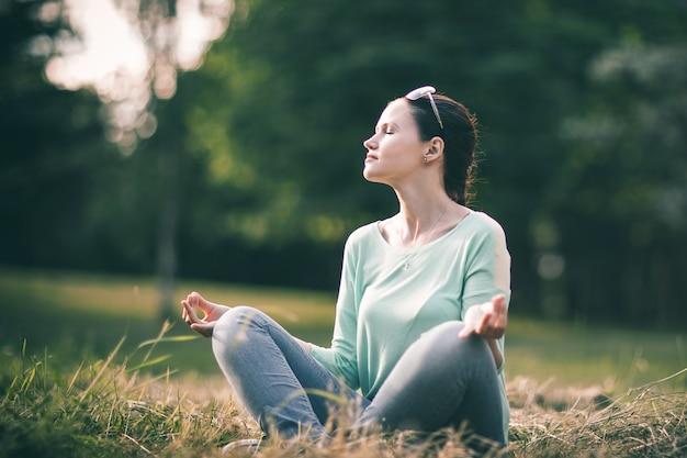 Piękna młoda kobieta medytując w pozycji lotosu. zdjęcie z miejsca na kopię