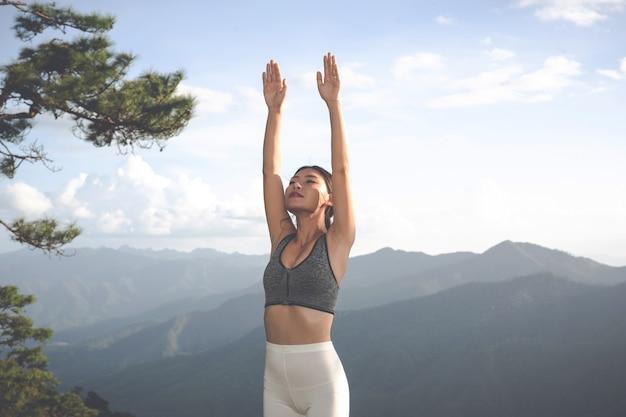 Piękna młoda kobieta medytuje i ćwiczy na nim.