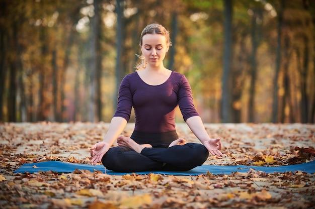 Piękna młoda kobieta medytuje w asana jogi padmasana - lotos stanowią na drewnianym pokładzie w parku jesień.