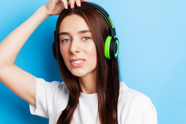 Piękna młoda kobieta model słucha muzyki w słuchawkach na niebiesko
