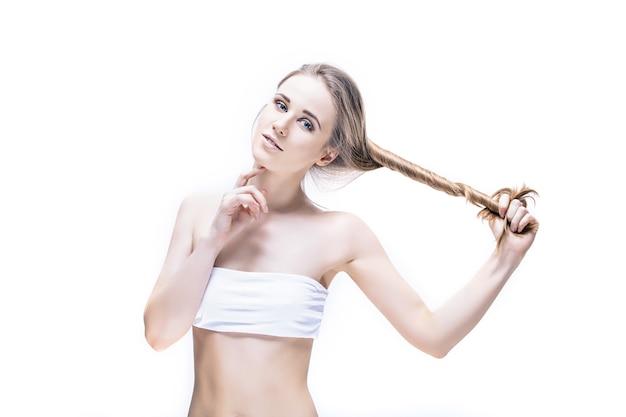 Piękna młoda kobieta model z długimi blond włosami i naturalnym makijażem, pozowanie na białym tle