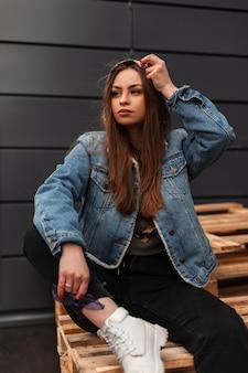Piękna młoda kobieta modelka w modne ubrania jeansowe w stylowe białe buty spoczywa na drewnianych deskach w pobliżu szarego budynku. miejska ładna, nowoczesna, modna dziewczyna siedzi na drewnianych paletach na zewnątrz