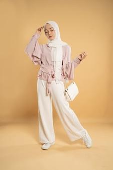Piękna młoda kobieta muzułmanin azji, na jasnym tle na białym tle, ubrana w nowoczesny styl hidżabu