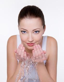 Piękna młoda kobieta myje twarz wodą