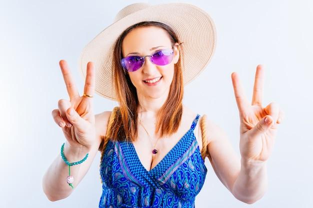 Piękna młoda kobieta na białym tle co znak v ubrana w słomkowy kapelusz, fioletowa letnia sukienka i okulary. koncepcja przyjazdu na wakacje