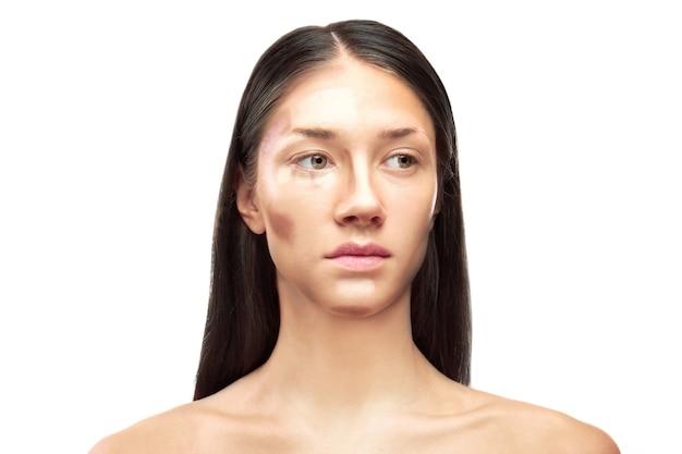 Piękna młoda kobieta na białym tle. profesjonalny makijaż konturujący twarz
