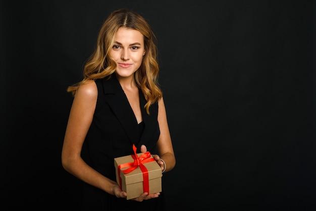 Piękna młoda kobieta na czarnym tle trzyma świąteczny prezent z czerwoną wstążką.