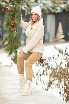 Piękna młoda kobieta na huśtawce na śnieżny zimowy spacer. zabawa na świeżym powietrzu na ferie zimowe.