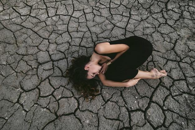 Piękna młoda kobieta na popękanej ziemi w czarnej sukni