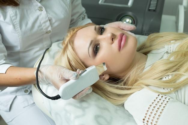 Piękna młoda kobieta na procedurę czyszczenia twarzy w kosmetologii