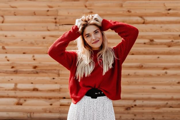 Piękna młoda kobieta na sobie ładną białą sukienkę i czerwony sweter, pozowanie w pobliżu drewnianego domu. uroczy blondyn wyglądający na szczęśliwego jesienią.