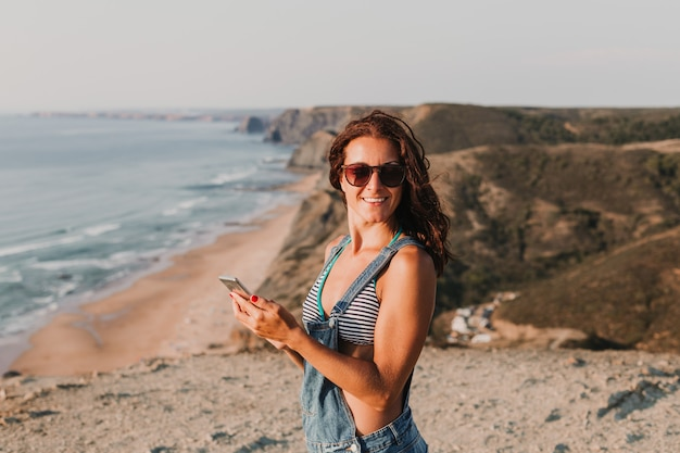 Piękna młoda kobieta na szczycie wzgórza używać jej telefon komórkowego i ono uśmiecha się. czas letni styl życia